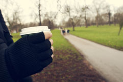 Man with a hot drink in a paper cup in Hyde Park in London, Unit. Closeup of a young caucasian man very sheltered wearing fingerless gloves holds a hot drink in Stock Photo