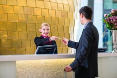 Hotel receptionist check in man giving key card. Man in Hotel check in at reception or front office being given key card Stock Image