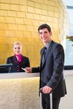 Hotel receptionist check in man giving key card stock images