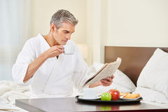 Man in hotel room reading newspaper Royalty Free Stock Photo