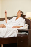 Man in hotel room reading text message Stock Images