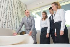 Man with hotel staff holding bedspread. Hotel royalty free stock image