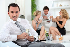 Man at a house party. Man drinking a glass of champagne at a house party Stock Images