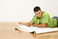 Man with house plans. Attractive man lying on floor in home reading house plans Royalty Free Stock Photo