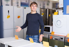 Man at household appliances store. Portrait of ordinary young man 25s at household appliances store Royalty Free Stock Photos
