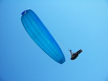 Man hovering on a blue paraglider Stock Photos