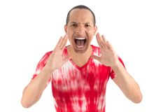 Man is howling. He is Latin American and is wearing a red and wh. Brave man shouts into the camera. Young latin american man wearing white and red shirt. White Stock Photos