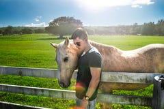 Man hug white horse on rancho farm at sunny summer day. royalty free stock photos