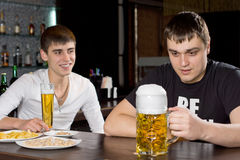 Man with a huge tankard of beer. Staring at it in fascination while his friend looks on with a smile of amusement as they sit together at the bar counter Royalty Free Stock Photos