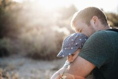 Man Hugging the Baby in Blue Floral Fitted Cap during Daytime Stock Photography