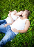Man hugging girlfriend on grass Stock Images
