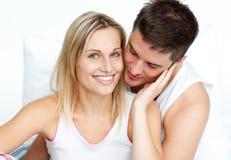 Man hugging his girlfriend in bed Stock Image