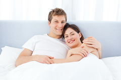 Man hugging his girlfriend on their bed Royalty Free Stock Image