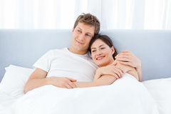 Man hugging his girlfriend on their bed Stock Image