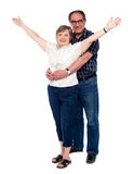 Man hugging his wife from behind. While women standing with arms wide open Royalty Free Stock Photography