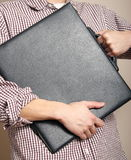 Man hugging a portfolio. A man wearing a checkered knit shirt hugging his portfolio Stock Images