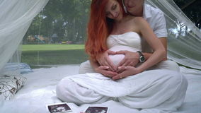 Man hugging pregnant woman in romantic decorations at park. Love couple stock video footage