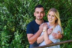 Man hugging smiling blonde girlfriend behind gate Royalty Free Stock Photography