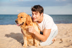 Man hugging and talking with dog on the beach Stock Photos
