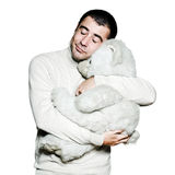 Man hugging teddy bear with eyes closed. Portrait of a caucasian man hugging a teddy bear in studio on white isolated background Royalty Free Stock Photography