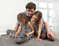 Man hugging two young girls looking at tablet Royalty Free Stock Image