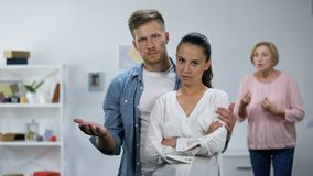 Man hugging wife, defending from angry mother quarrelling, misunderstanding. Stock footage stock footage