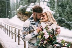 Man hugging woman on wooden bridge in mountain. Young pretty pair of lovers. Winter. Date. Man hugging women on wooden bridge in mountain Royalty Free Stock Images