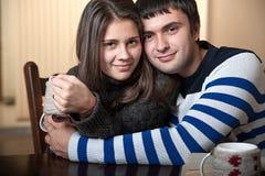 Man huging a woman. Man hugs a women that drinks tea Stock Images