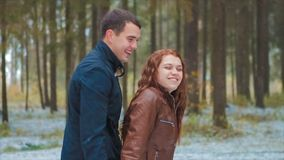 Man hugs girlfriend in winter forest. Man hugs Young woman, they standing together laughing by falling snowflakes. It`s Autumn or Early Winter With Snow on stock video