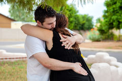 Man Hugs Wife Through Labor Contraction. A men holds his wife outdoors as she is having a labor contraction Stock Photos