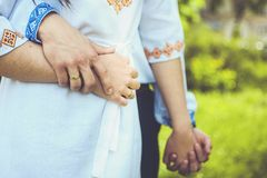 Man hugs woman and holding hand in ukrainian traditional clothes. Embroidered clothes by blue and yellow colors stock photography