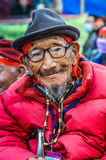 Man with humble smile in Bihar. Bohdgaya, Bihar - circa January 2012: Old man with wrinkled face and black hat on his head wears glasses with humble smile in Royalty Free Stock Photos