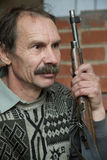Man the hunter with a rifle. Sitting in the room Stock Images