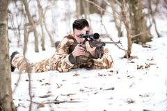 Man hunter shooting with a sniper rifle, aiming and firing bullets Stock Photography