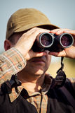 Man hunter with shotgun looking through binoculars in forest Stock Photography
