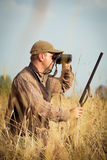 Man hunter with shotgun looking through binoculars in forest Royalty Free Stock Photography