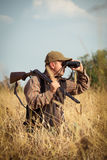 Man hunter with shotgun looking through binoculars in forest Stock Images