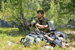 Man, hunter, sitting near the rifle and backpack in the taiga. Stock Photo