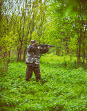 A man hunter take aim for a shot from a carbine, hunting in a spring forest in the rain Stock Photography