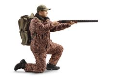 Man hunter in a uniform kneeling and aiming with a shotgun. Full length profile shot of a man hunter in a uniform kneeling and aiming with a shotgun isolated on royalty free stock photography