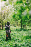 A man hunter wanders with a gun in rainy weather through a spring forest Royalty Free Stock Photography