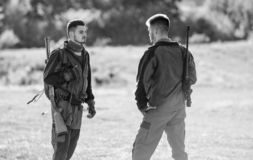 Man hunters with rifle gun. Boot camp. Friendship of men hunters. Army forces. Camouflage. Military uniform fashion. Hunting skills and weapon equipment. How stock photography