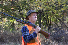 Man Hunting. Man carrying a shotgun while hunting in a field Stock Photo