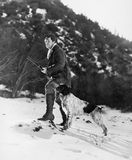 Man hunting in snowy mountains with dog. (All persons depicted are no longer living and no estate exists. Supplier grants that there will be no model release Stock Image