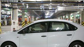 The man hurries on a meeting. Gets into the car and leaves an underground parking. Video contains a sound.  stock video