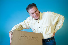 Man That Hurts!. A man with a grimace on his face holding his back as if injured due to lifting a box of books Royalty Free Stock Images
