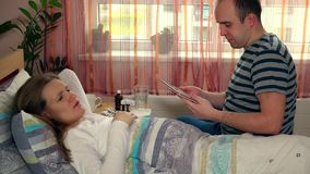 Man husband with tablet computer entertain his sick wife woman in bed. Dramatic color grading. Static shot. 4K UHD stock video
