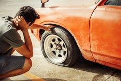 Man huvudvärken när bilsammanbrottet och rulla det plana gummihjulet i parkering royaltyfria bilder