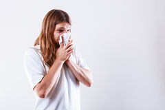 Man with hygienic tissue. Allergy and cold concept. Young long haired sick man with hygienic tissue. Guy blowing nose royalty free stock photo