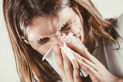 Man with hygienic tissue. Allergy and cold concept. Young long haired sick man with hygienic tissue. Guy blowing nose Royalty Free Stock Image